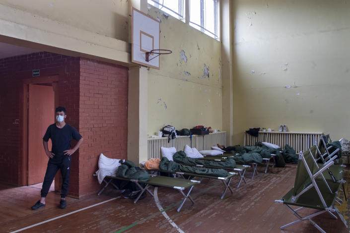 """A migrant from Iraq stands in a sport hall where refugees live in a school building at the refugee camp in the village of Verebiejai, some 145km (99,1 miles) south from Vilnius, Lithuania, Sunday, July 11, 2021. Lithuania has struggled with a flow of migrants from the Middle East and Africa, a huge influx that officials in the tiny Baltic country say was organized by Belarusian authorities as part of a """"hybrid war"""" against the European Union. (AP Photo/Mindaugas Kulbis)"""