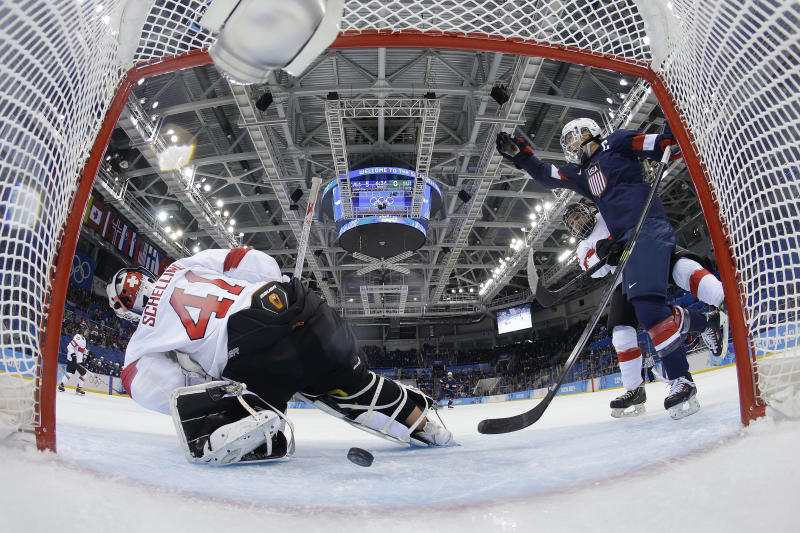 Meghan Duggan of the Untied States celebrates Monique Lamoureux's goal as the puck slides under Goalkeeper Florence Schelling of Switzerland during the second period of the 2014 Winter Olympics women's ice hockey game at Shayba Arena, Monday, Feb. 10, 2014, in Sochi, Russia. USA defeated Switzerland 9-0. (AP Photo/Matt Slocum)
