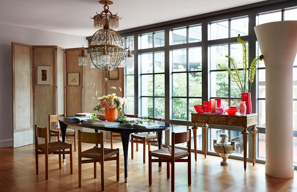 """<div class=""""caption""""> In the dining area, a Baguès chandelier once owned by Yves Saint Laurent and 1950s Charlotte Perriand chairs. </div> <cite class=""""credit"""">Stephen Kent Johnson </cite>"""
