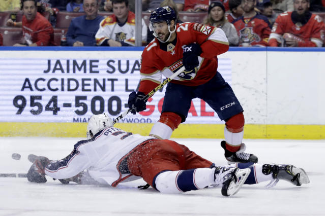 Columbus Blue Jackets defenseman Andrew Peeke, left falls to the ice as he goes for the puck against Florida Panthers center Vincent Trocheck (21) during the second period of an NHL hockey game, Saturday, Dec. 7, 2019, in Sunrise, Fla. (AP Photo/Lynne Sladky)