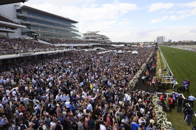 FIEL - In this Nov. 6, 2018, file photo, fans watch as horses enter the track during the Melbourne Cup at Flemington Racecourse in Melbourne. In Australia, where horse racing is arguably more popular than in any other country on the planet, the sport is continuing, minus the spectators, despite the nation's struggle to contain the new coronavirus. (AP Photo/Andy Brownbill, File)