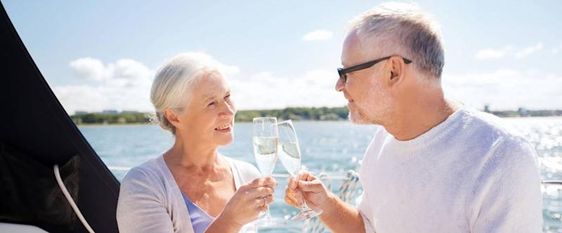senior couple clinking glasses on boat or yacht