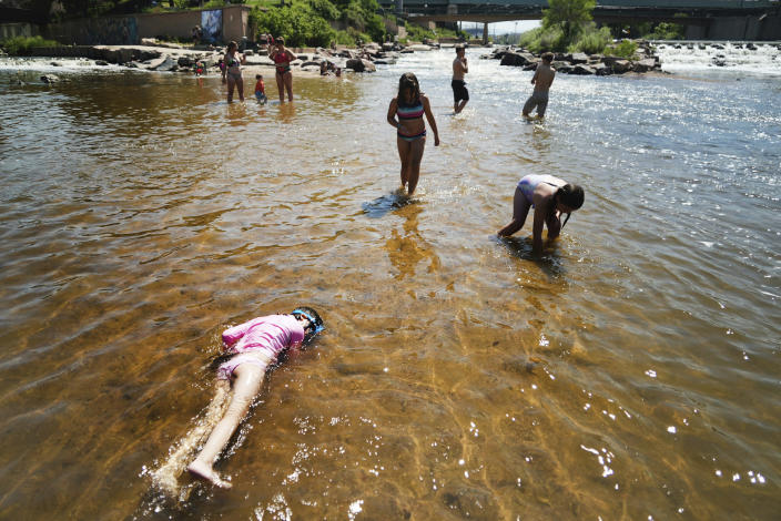 Children play in the water at the confluence of the South Platte River and Cherry Creek in Denver, Monday, June 14, 2021. By mid-afternoon, the temperature hit 96 degrees Fahrenheit as part of the heat wave sweeping across the Western United States.(AP Photo/Brittany Peterson)