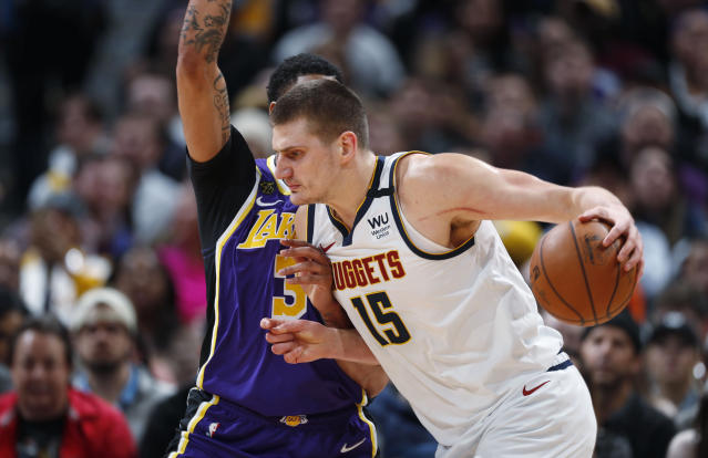 Denver Nuggets center Nikola Jokic drives as Los Angeles Lakers forward Anthony Davis defends during the first half of an NBA basketball game Wednesday, Feb. 12, 2020, in Denver. (AP Photo/David Zalubowski)