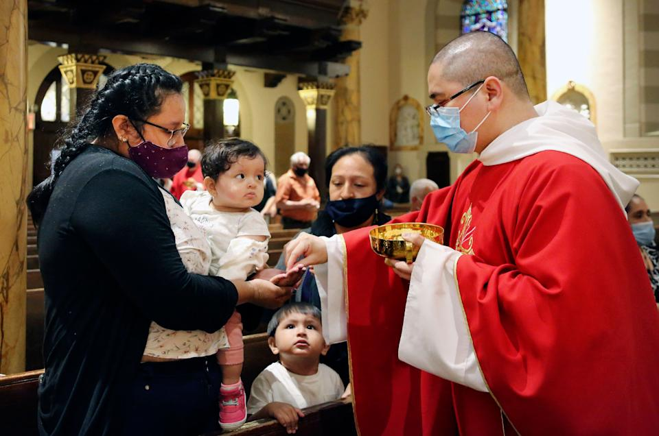 Parishioners receive the sacrament from the Rev. Luis Gabriel Medina during Communion at Saint Bartholomew Roman Catholic Church in the Queens borough of New York, July 6. (Photo: (AP Photo/Jessie Wardarski))
