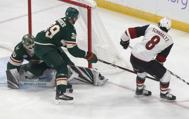 Minnesota Wild goalie Devan Dubnyk, left, stops a shot by Arizona Coyotes' Nick Schmaltz, right, during the first period of an NHL hockey game Tuesday, Nov. 27, 2018, in St. Paul, Minn. (AP Photo/Jim Mone)