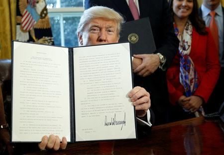 After signing, U.S. President Donald Trump holds up an executive order rolling back regulations from the 2010 Dodd-Frank law on Wall Street reform at the White House in Washington February 3, 2017.  REUTERS/Kevin Lamarque