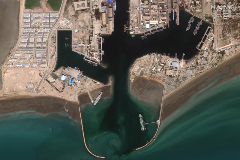 In this Feb. 15, 2020, satellite photo provided on July 27, 2020, by Maxar Technologies, a mockup aircraft carrier, center left, built by Iran is seen at Bandar Abbas, Iran, before being put to sea. Satellite photographs released Monday, July 27, showed Iran has moved the aircraft carrier out to sea likely for naval drills amid heightened tensions between Tehran and the U.S. (Maxar Technologies via AP)