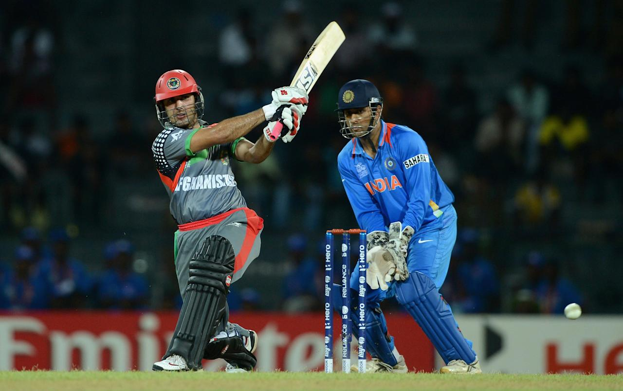 COLOMBO, SRI LANKA - SEPTEMBER 19:  Mohammad Nabi of Afghanistan bats watched by India wicketkeeper MS Dhoni during the  ICC World Twenty20 2012: Group A match between India and Afghanistan at R. Premadasa Stadium on September 19, 2012 in Colombo, Sri Lanka.  (Photo by Gareth Copley/Getty Images,)