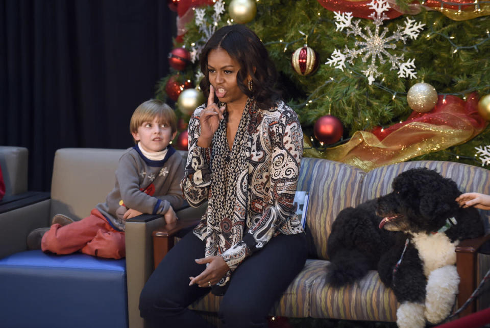 <p>Michelle Obama brought along one of her fluffy Portuguese water dogs to read <i>'Twas the Night Before Christmas</i> to kids at the Children's National Health System. For the occasion, she wore a paisley print top with an attached scarf and navy blue trousers. <i>Photo: AP</i></p>