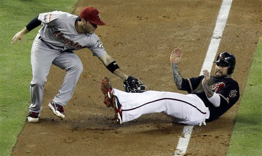 Arizona Diamondbacks' Ryan Roberts, right, gets tagged out in a run down by Houston Astros' Jose Altuve in the second inning during a baseball game Saturday, July 21, 2012, in Phoenix. (AP Photo/Ross D. Franklin)