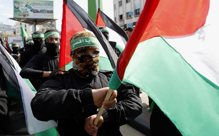FILE - In this Feb. 21, 2020, file photo, masked Hamas militants wave their national flags during a protest in Gaza City. On Thursday, April 29, 2021, Hamas rejected the idea of postponing Palestinian elections ahead of a leadership meeting in which President Mahmoud Abbas' Fatah party is expected to push for a delay, citing a dispute with Israel over voting in east Jerusalem. (AP Photo/Adel Hana, File)