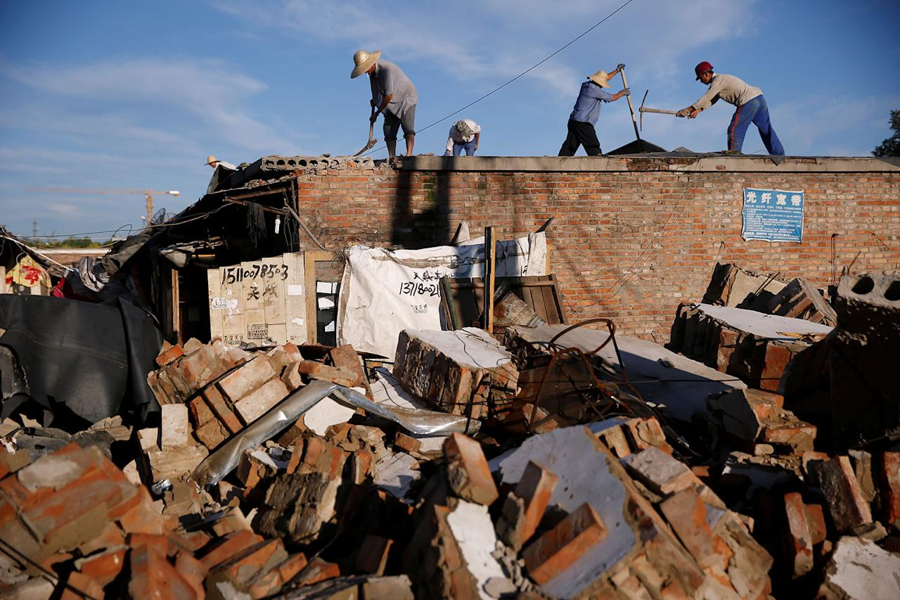 <p>Workers prepare concrete roof slabs for removal from former migrant dwellings before their destruction at Dongsanqi village in the outskirts of Beijing, China, August 7, 2017. (Photo: Thomas Peter/Reuters) </p>