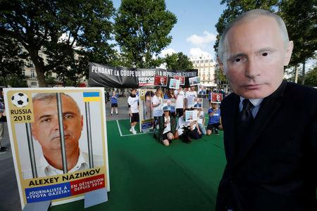 A Reporter Without Borders (RSF) activist, wearing a mask depicting Russian President Vladimir Putin, stands next to a giant portrait of journalist Alexey Nazimov on Place de la Republique, transformed into a soccer field to denounce abuse of press freedom in Russia before the start of the 2018 FIFA World Cup Russia, in Paris, France, June 13, 2018.  REUTERS/Philippe Wojazer