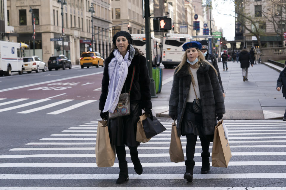 FILE - Women carry shopping bags, Thursday, Dec. 10, 2020, in New York. Shoppers, who can't touch or feel products they're ordering, are expected to return items during the holiday season at a rate double from last year, costing retailers roughly $1.1 billion, according to Narvar Inc., a software and technology company that manages online returns for hundreds of brands. That puts retailers in a conundrum: they don't want the returns, but they also want to make shoppers feel comfortable to freely buy without worry. (AP Photo/Mark Lennihan)