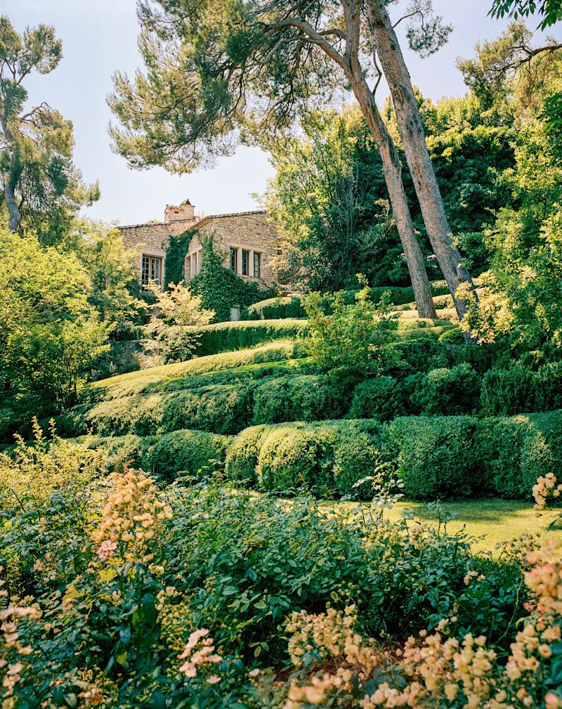Boxwood tiers rise to the stone guesthouse.