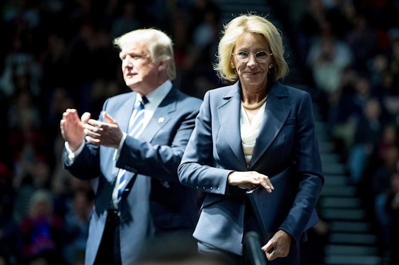 President-elect Donald Trump, left, applauds after his pick for Education Secretary Betsy DeVos, right, finishes speaking at a rally at DeltaPlex Arena, Friday, Dec. 9, 2016, in Grand Rapids, Mich. (AP Photo/Andrew Harnik)