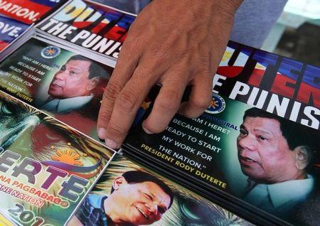 A vendor sells souvenir items with images of Philippine President Rodrigo Duterte in Davao city in southern Philippines, August 5, 2017. REUTERS/Lean Daval Jr/Files