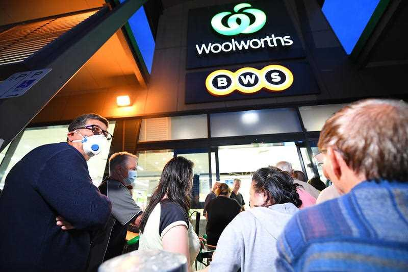 People are seen waiting in line outside a Woolworths supermarket in Coburg, Melbourne.