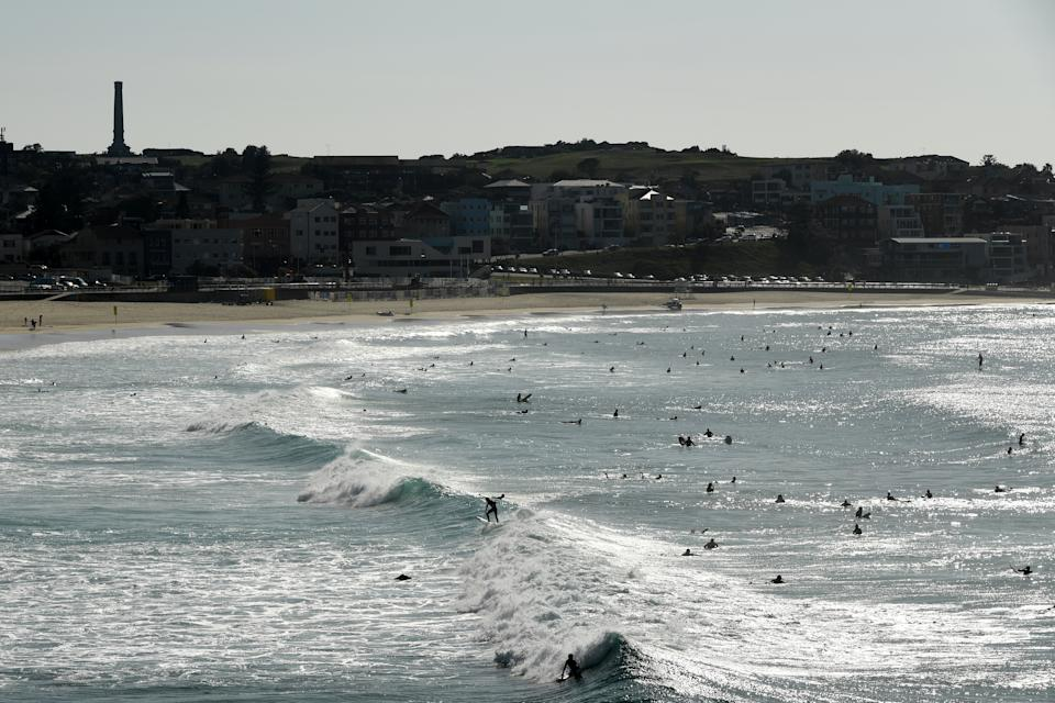 Surfers are seen in the water at a closed Bondi Beach on Sunday. Source: AAP