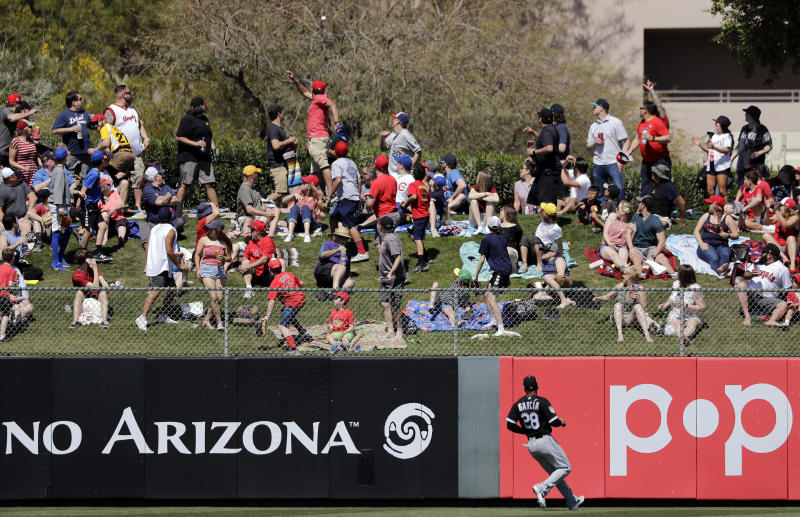 Chicago White Sox left fielder Leury Garcia watches with fans as a home run ball off Los Angeles Angels' Mike Trout flies into trees behind in the first inning of a spring training baseball game Friday, March 22, 2019, in Tempe, Ariz. (AP Photo/Elaine Thompson)
