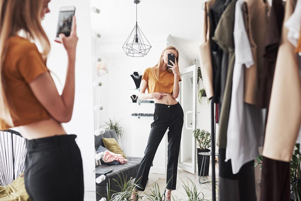 female influencer taking a photo of her outfit in a full length mirror