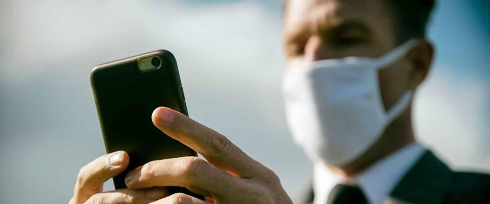 Worried businessman wearing surgical face mask checking his smartphone for coronavirus news updates outdoors