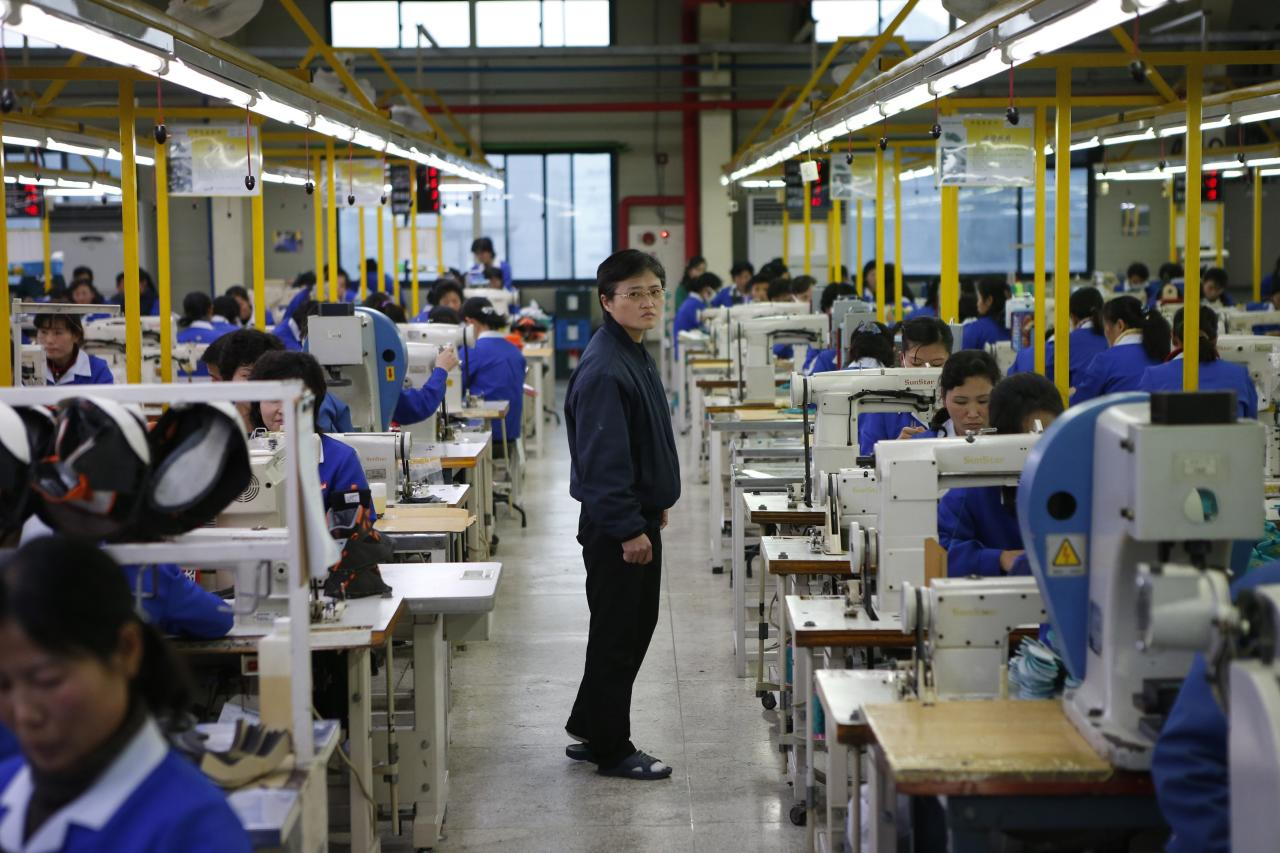 A North Korean manager walks down an aisle as employees work in a factory of a South Korean company at the Joint Industrial Park in Kaesong industrial zone