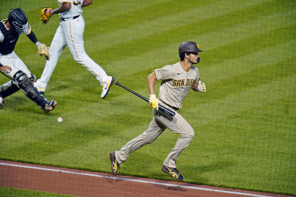 San Diego Padres starting pitcher Yu Darvish carries his bat as he runs to first base as Pittsburgh Pirates catcher Jacob Stallings, left, fields the ball to make the putout on him at first base to end the top of the sixth inning during a baseball game in Pittsburgh, Monday, April 12, 2021. (AP Photo/Gene J. Puskar)