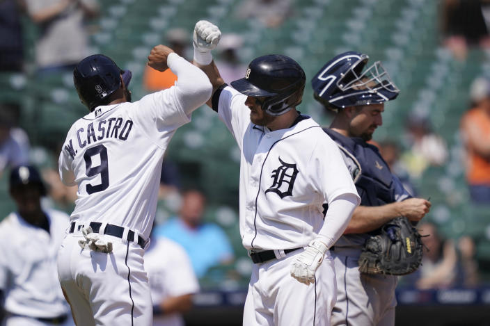 Detroit Tigers' Willi Castro greets Robbie Grossman next to Seattle Mariners catcher Tom Murphy after they scored on Grossman's two-run home run during the sixth inning of a baseball game, Thursday, June 10, 2021, in Detroit. (AP Photo/Carlos Osorio)