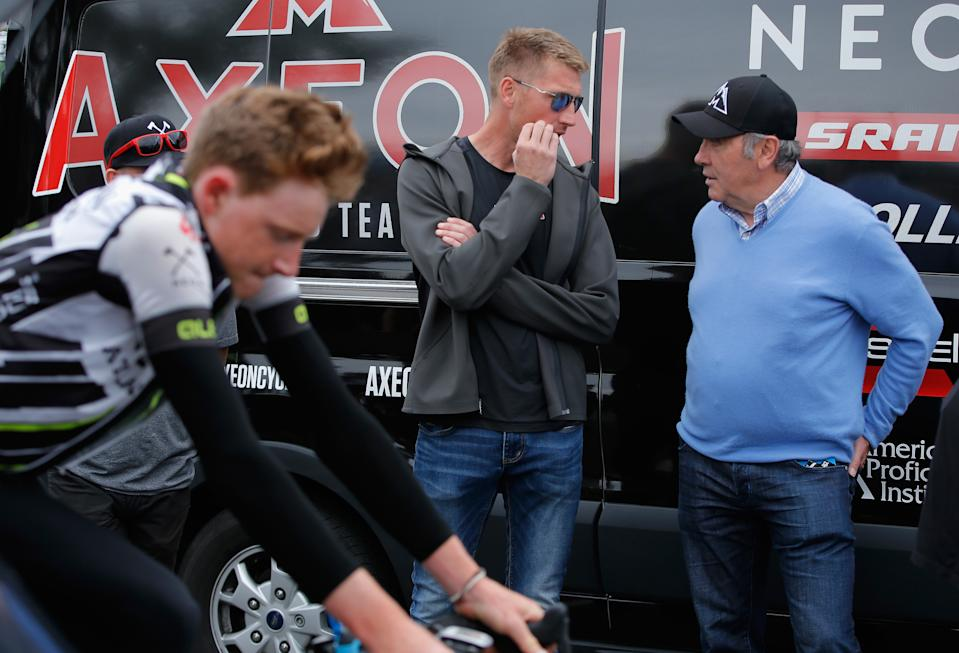 ONTARIO, CA - MAY 16:  Axel Merckx (C) director of the Axeon Cycling Team talks with his father Eddy Merckx (R) as Tao Geoghegan Hart (L) of Great Britain riding for Axeon Cycling warms up prior to the start of stage seven of the 2015 Amgen Tour of California from Ontario to Mt. Baldy on May 16, 2015 in Ontario, California.  (Photo by Doug Pensinger/Getty Images)