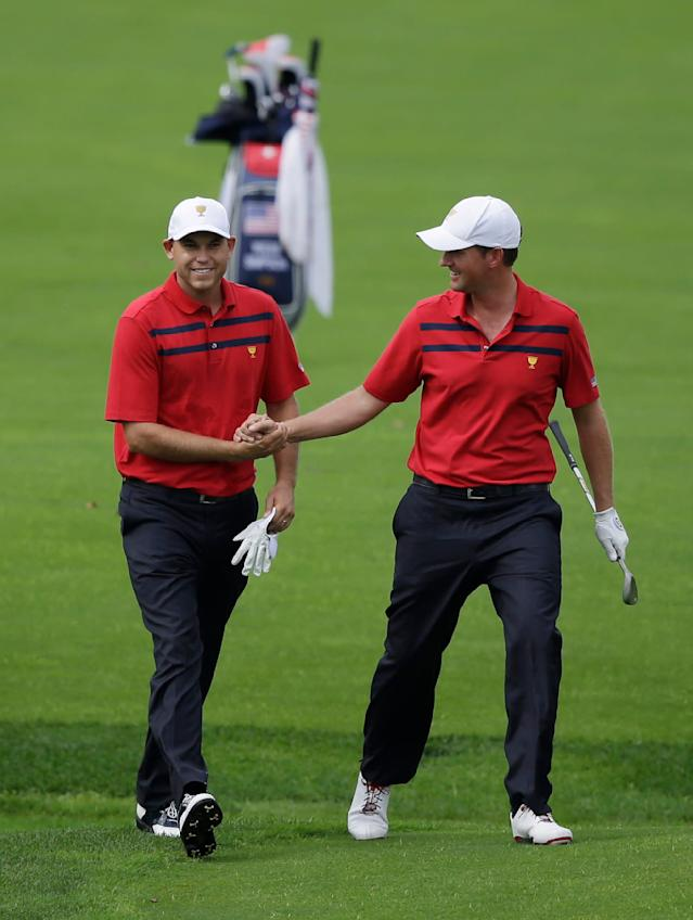 United States' Bill Haas is congratulated by Webb Simpson after Haas hit his second shot on to the 14th green during the four-ball matches at the Presidents Cup golf tournament at Muirfield Village Golf Club Saturday, Oct. 5, 2013, in Dublin, Ohio. Haas and Simpson defeated the International's Angel Cabrera, of Argentina, and Branden Grace, of South Africa, 4 and 3. (AP Photo/Darron Cummings)
