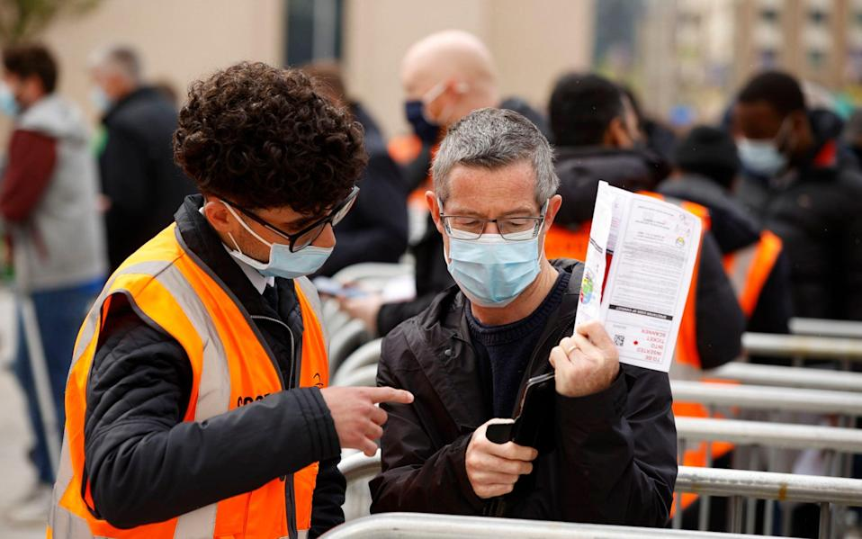 fan shows their Covid-19 test result and ticket to a steward at the stadium before the match - Reuters