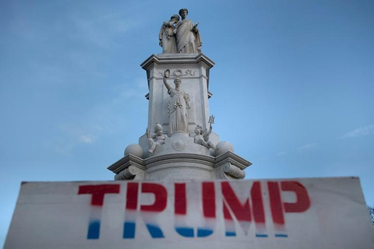 A sign is seen left near a statue on Capitol Hill a day after a pro-Trump mob broke into the Capitol