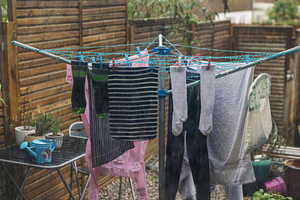 Rain soaked laundry hanging on a clothesline in back garden