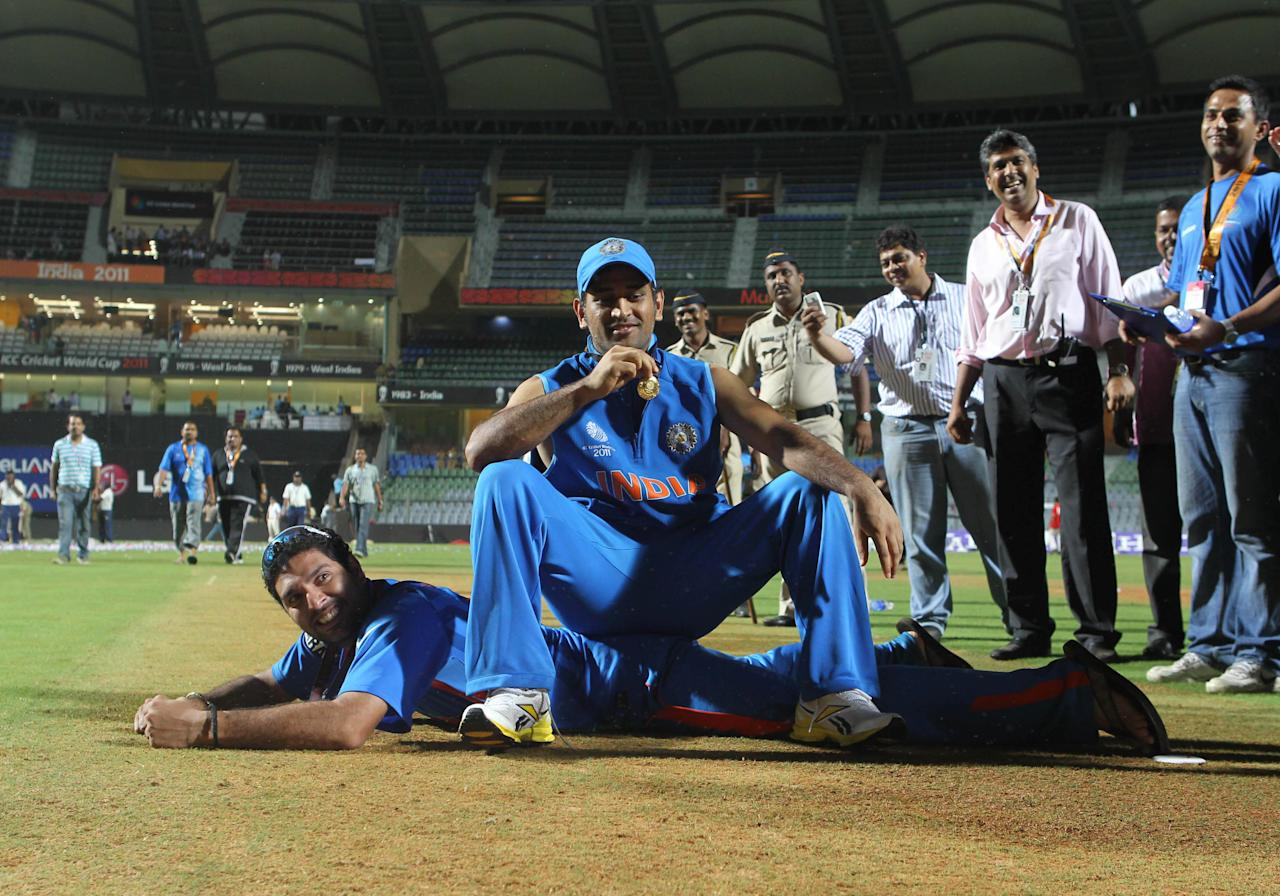 MUMBAI, INDIA - APRIL 2:  Indian captain Mahendra Singh Dhoni and Man of the Tournament Yuvraj Singh pose on the wicket after India won the final of 2011 ICC World Cup beating Sri Lanka by 6 wickets at Wankhede stadium in Mumbai, India on April 2, 2011. (Photo by Santosh Harhare/Hindustan Times via Getty Images)