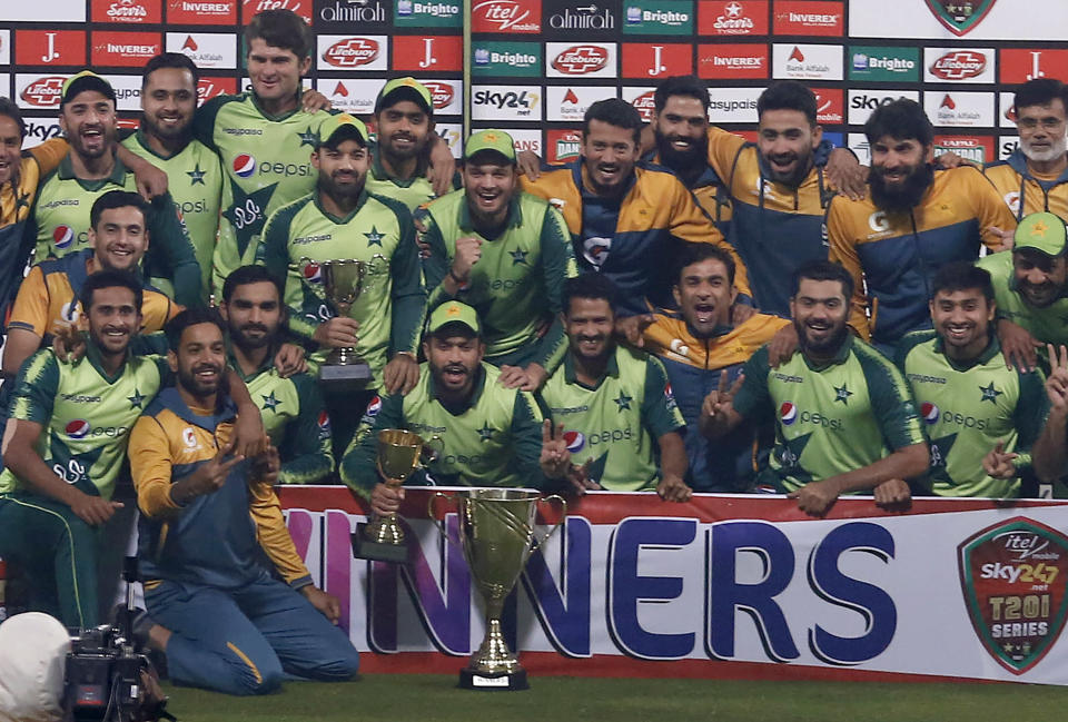 Pakistani players and officials pose for a photograph with the winning trophy of the Twenty20 series against South Africa at the end of of the third Twenty20 cricket match between Pakistan and South Africa at the Gaddafi Stadium, in Lahore, Pakistan, Sunday, Feb. 14, 2021. (AP Photo/K.M. Chaudary)
