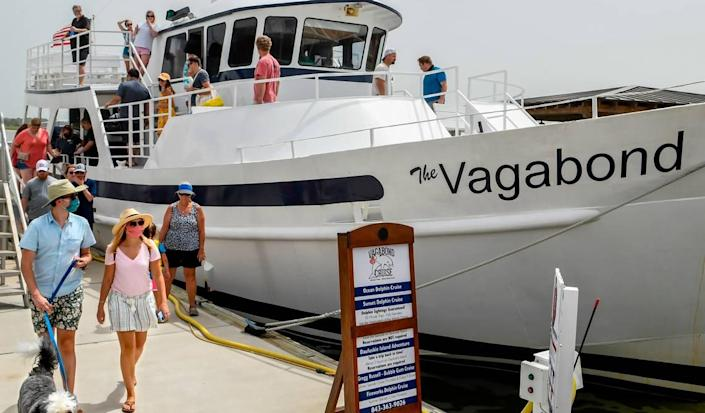 Before the mandatory mask requirement, two guests wearing face coverings disembark from The Vagabond Cruise on Saturday, June 27, 2020 at Harbour Town in Sea Pines on Hilton Head Island after a sight seeing cruise.