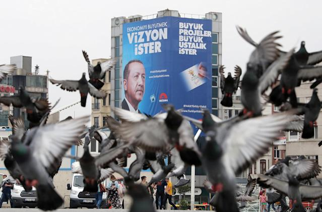 Pigeons fly in front of a large election poster of Turkish President Tayyip Erdogan in Istanbul,Turkey, June 22, 2018. REUTERS/Goran Tomasevic TPX IMAGES OF THE DAY