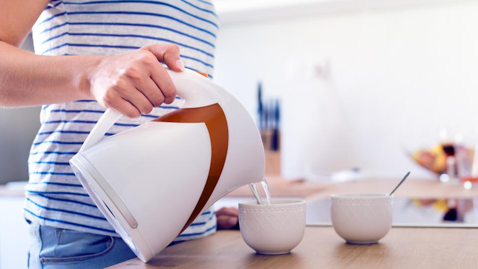 Unrecognizable woman preparing coffee or tea. Pouring water into a cup.