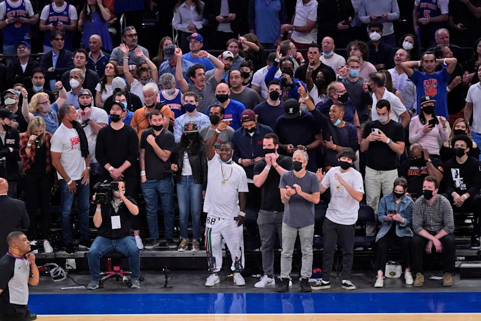 Fan, including Tracy Morgan and John Stewart (both front center), rise to their feet during the final moments of the NBA playoff game between the Atlanta Hawks and the New York Knicks.
