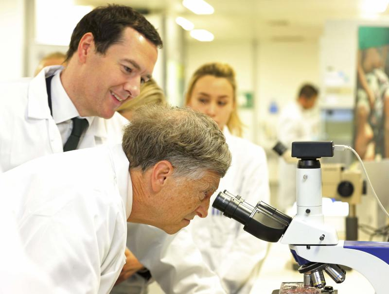 Microsoft co-founder Bill Gates looks through a microscope during a tour with Britain's Chancellor George Osborne to the Liverpool School of Tropical Medicine in Liverpool