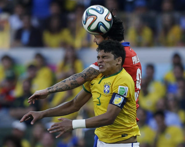 Brazil's Thiago Silva wins a challenge with Chile's Mauricio Pinilla during the World Cup round of 16 soccer match between Brazil and Chile at the Mineirao Stadium in Belo Horizonte, Brazil, Saturday, June 28, 2014. (AP Photo/Andre Penner)