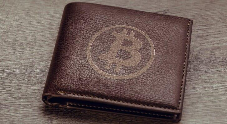 Image shows a brown wallet with the Bitcoin symbol stamped on it. If you own Bitcoin, you can use a cold storage wallet to store it offline, which keeps it safe from hacking and other web attacks.