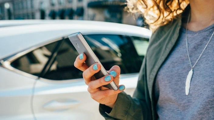 Woman using phone to summon a taxi