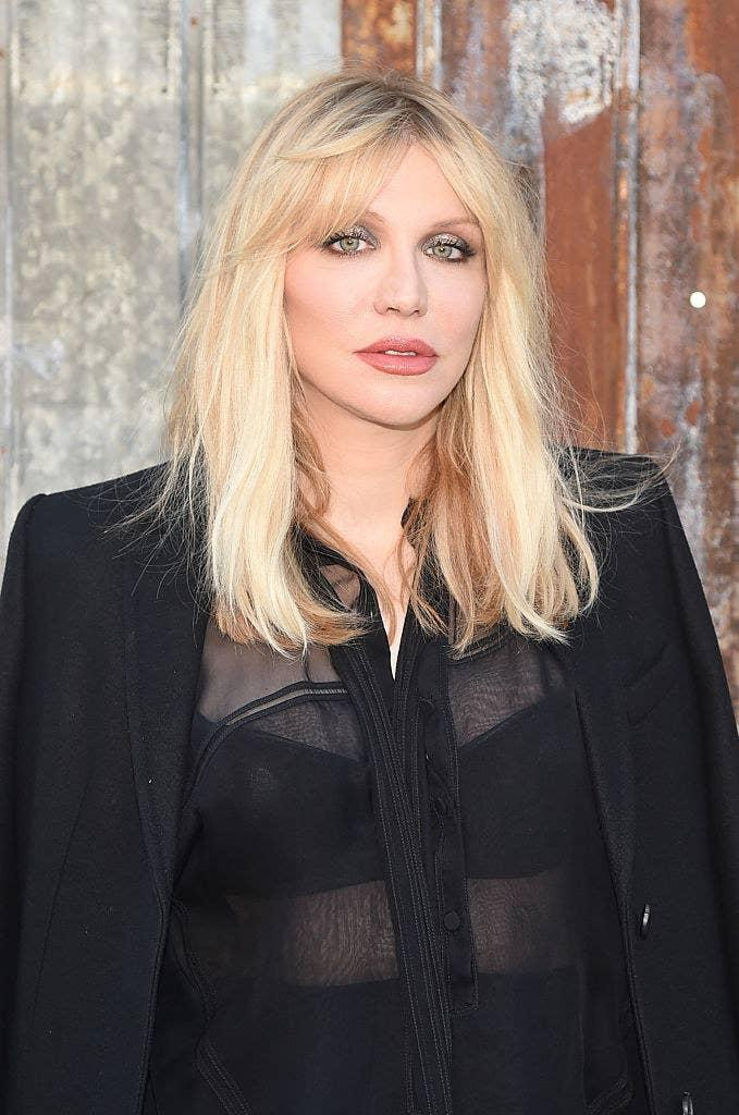 Courtney wearing a black transparent top and jacket