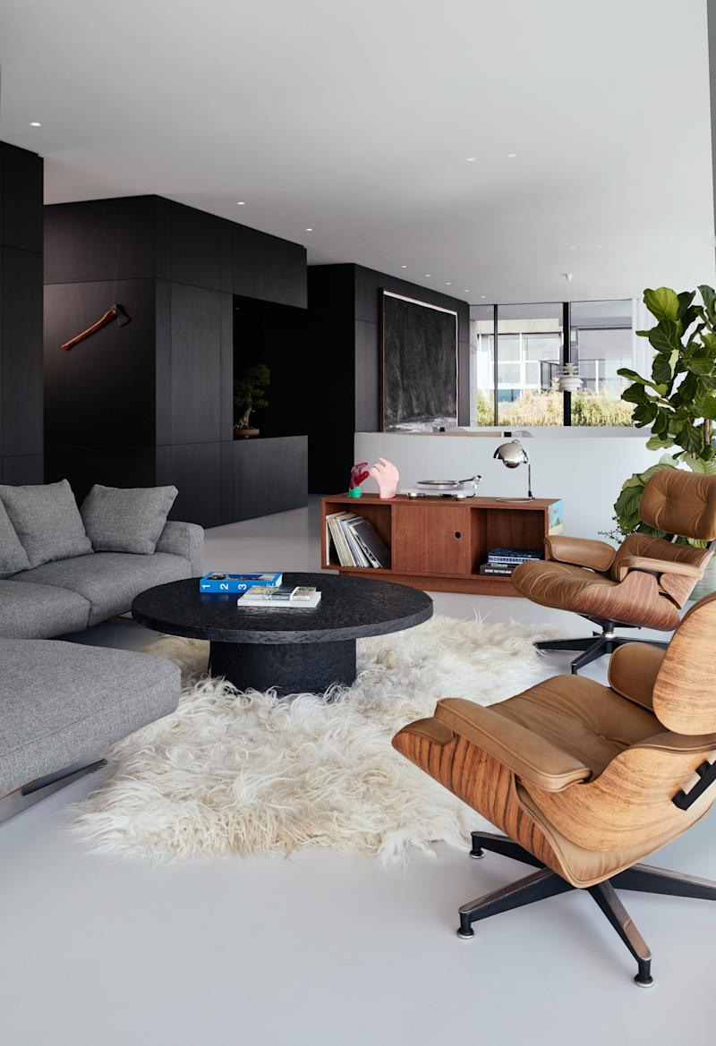The living room features a vintage brutalist coffee table and two rare cream-colored Eames chairs, both sourced by vintage specialists Morentz. The carpet is handmade from the wool of biodynamic Dutch sheep.