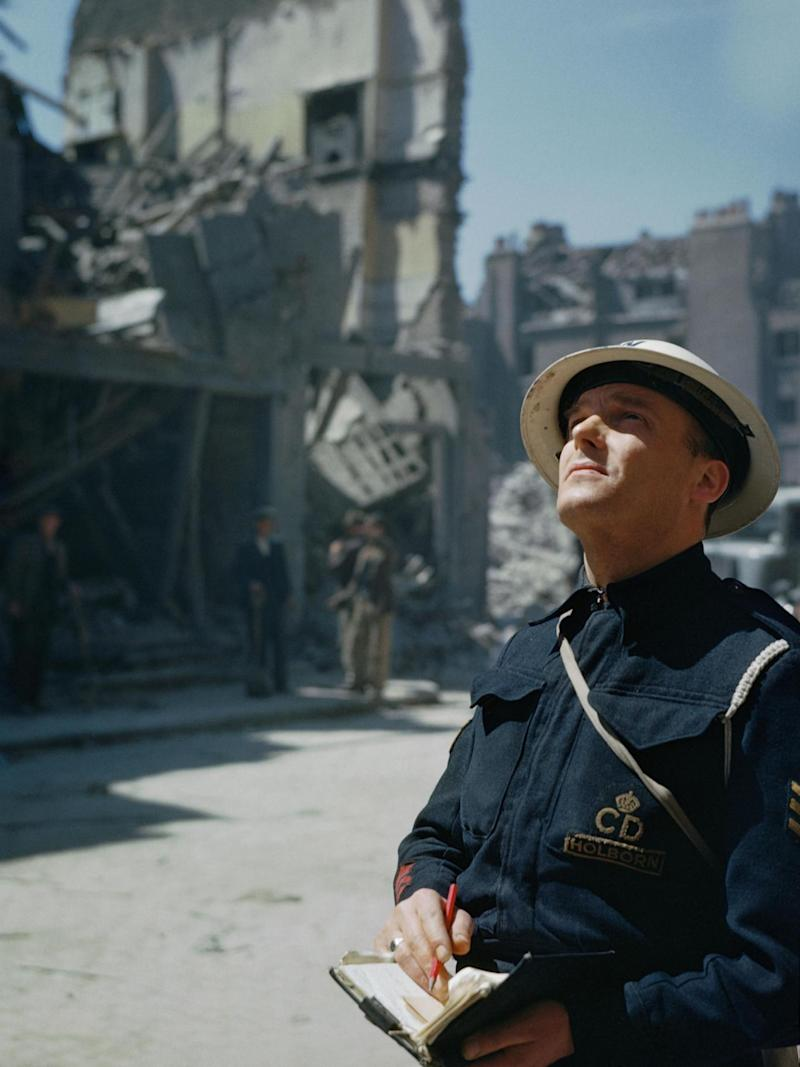 An Air Raid Precautions (ARP) warden inspecting damaged buildings in Holborn, London (Imperial War Museum )