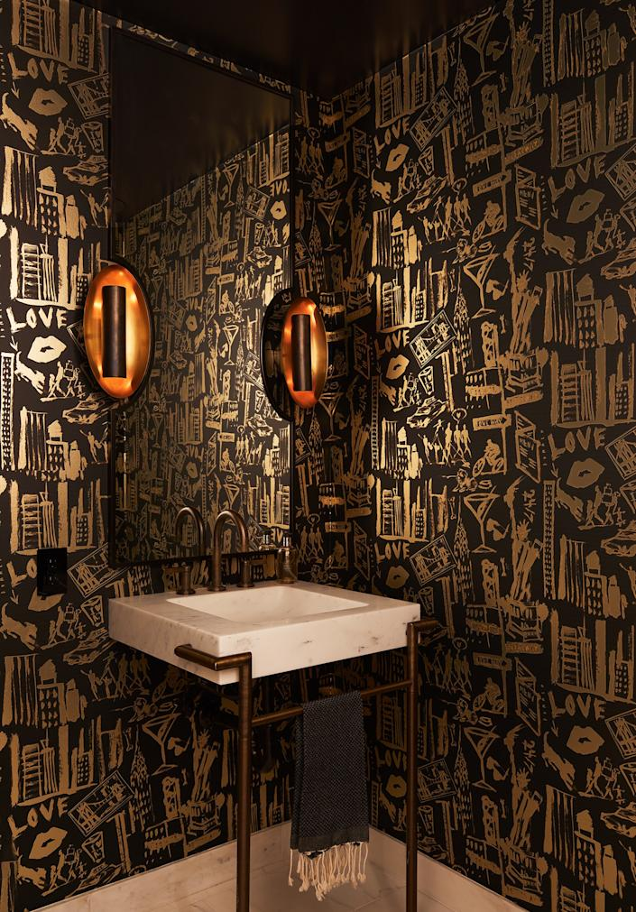 "<div class=""caption""> The powder room features custom wallpaper by Donald Robertson from <a href=""https://www.astek.com/"" rel=""nofollow noopener"" target=""_blank"" data-ylk=""slk:Astek Printing"" class=""link rapid-noclick-resp"">Astek Printing</a>. ""It has references to Broadway and martinis and eating out and a dog and us. It's sort of an homage to our life. So, that's really special,"" says Ferguson. The sconces are by <a href=""https://www.circalighting.com/"" rel=""nofollow noopener"" target=""_blank"" data-ylk=""slk:Circa Lighting"" class=""link rapid-noclick-resp"">Circa Lighting</a> and the mirror is custom designed by Gurski and fabricated by <a href=""https://www.kaufmaniron.com/"" rel=""nofollow noopener"" target=""_blank"" data-ylk=""slk:Kaufman Iron Works"" class=""link rapid-noclick-resp"">Kaufman Iron Works</a>. </div>"