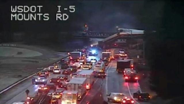 <p>A still image from a video camera shows an Amtrak train that derailed on a bridge over a highway in Pierce County, Washington state, U.S., December 18, 2017. (Photo: WSDOT via REUTERS) </p>